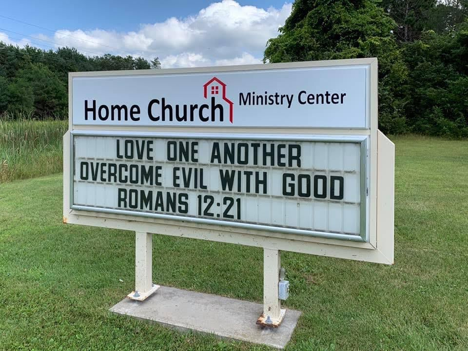 Love one another. Overcome evil with good. Romans 12:21. Sign at Home Church Ministry Center.